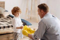 Enfant attentif ajoutant un certain liquide de nettoyage Photos libres de droits