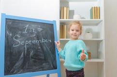 Enfant au conseil de craie avec l'inscription le 1er septembre Image stock