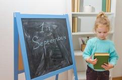 Enfant au conseil de craie avec l'inscription le 1er septembre et Photographie stock libre de droits