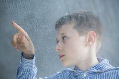 Enfant autiste comptant des gouttes de pluie Photos libres de droits