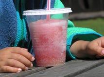 Enfant avec de la glace rouge de neige fondue Photographie stock
