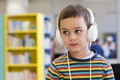 Enfant avec des écouteurs dans l'école ou la bibliothèque Photographie stock