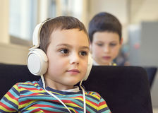 Enfant avec des écouteurs dans l'école ou la bibliothèque Images libres de droits