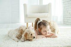Enfant avec des chiots de Labrador à la maison sur le tapis photographie stock