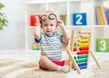 Enfant avec des lunettes jouant l'abaque Image stock