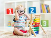 Enfant avec des lunettes jouant l'abaque Images libres de droits