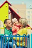 Enfant avec des parents à un terrain de jeu Photographie stock libre de droits