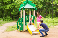 Enfant avec des parents au terrain de jeu Maman, papa et fille Jeu du famille Images libres de droits