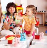 Enfant avec des peintures d'attraction de professeur dans la chambre de pièce. Images stock