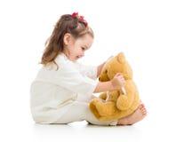 Enfant avec des vêtements de docteur jouant avec le jouet Photos stock