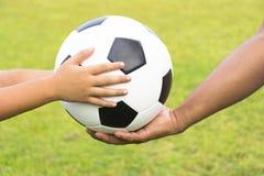 Enfant avec du ballon de football et l'entraîneur sur l'herbe verte de fond Images libres de droits