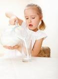 Enfant avec du lait en verre de pichet photos stock