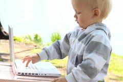 Enfant avec l'ordinateur portatif photos stock