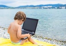 Enfant avec l'ordinateur sur la plage près de la mer Image libre de droits