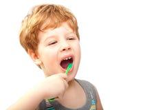 Enfant avec la brosse à dents d'isolement sur le blanc Image stock