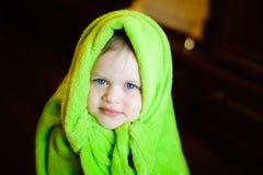 Enfant avec la couverture verte d'ouatine sur sa tête sur un fond foncé Photo libre de droits