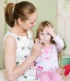 Enfant avec la grosse fièvre et la mère prenant la température Photo libre de droits