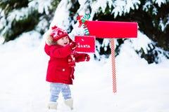 Enfant avec la lettre à Santa à la boîte aux lettres de Noël dans la neige Photos stock