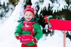 Enfant avec la lettre à Santa à la boîte aux lettres de Noël dans la neige Images stock