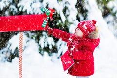 Enfant avec la lettre à Santa à la boîte aux lettres de Noël dans la neige Image libre de droits