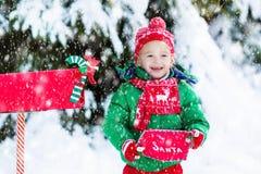 Enfant avec la lettre à Santa à la boîte aux lettres de Noël dans la neige Image stock