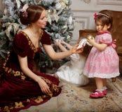Enfant avec la mère recevant près de l'arbre de Noël Photographie stock