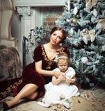 Enfant avec la mère recevant près de l'arbre de Noël Photos stock