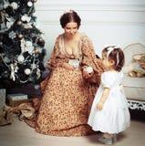 Enfant avec la mère recevant près de l'arbre de Noël Photo libre de droits