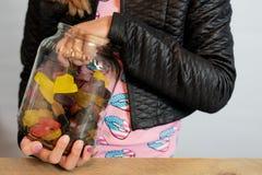 Enfant avec la main dans le pot de sucrerie sucrerie de saisie hors du pot Section médiane de corps de Childs image stock
