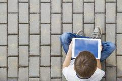 Enfant avec la tablette se reposant dehors Éducation, apprenant, technologie, amis, concept d'école Vue supérieure Image stock