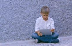 Enfant avec la tablette se reposant dehors Photo libre de droits