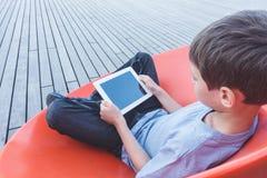 Enfant avec la tablette se reposant dehors Image libre de droits