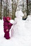 Enfant avec le bonhomme de neige en stationnement de l'hiver Photographie stock libre de droits