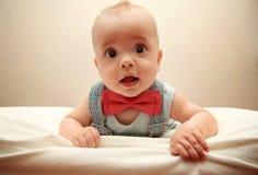 Enfant avec le bowtie se trouvant sur le lit Image libre de droits