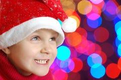 Enfant avec le chapeau de Santa au-dessus des lumières photos stock