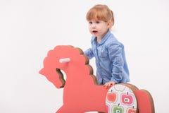 Enfant avec le cheval de jouet Photo stock