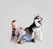 Enfant avec le chien de traîneau de chiot Photo stock