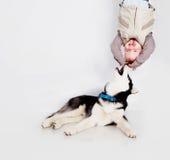 Enfant avec le chien de traîneau de chiot Images libres de droits