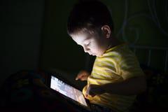 Enfant avec le comprimé dans l'obscurité Images stock