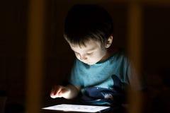 Enfant avec le comprimé dans l'obscurité Photos libres de droits