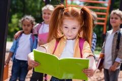 Enfant avec le livre sur le terrain de jeu Photo libre de droits