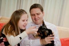 Enfant avec le père jouant avec le chien Image stock
