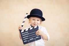 Enfant avec le panneau de clapet jouant ? la maison photos libres de droits