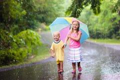 Enfant avec le parapluie jouant sous la pluie d'été Photographie stock libre de droits