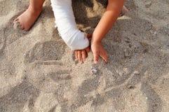 Enfant avec le plâtre sur sa main jouant dans le sable sur la plage par la mer photographie stock libre de droits
