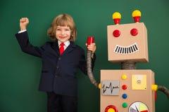 Enfant avec le robot de jouet à l'école Image libre de droits