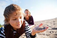 Enfant avec le sable à disposition à la plage. Image libre de droits
