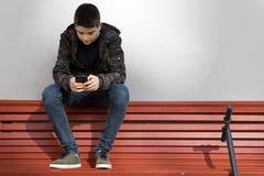 Enfant avec le téléphone de téléphone dans la rue Photographie stock libre de droits