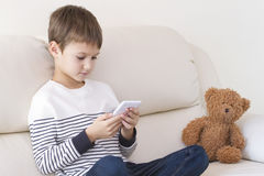 Enfant avec le téléphone portable à la maison Garçon jouant, apprenant, lisant quelque chose photos libres de droits