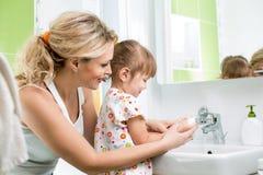 Enfant avec les mains de lavage de maman Images stock